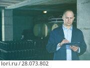 Купить «Wine producer with clipboard in wine cellar», фото № 28073802, снято 22 января 2018 г. (c) Яков Филимонов / Фотобанк Лори