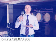 Купить «Confident winemaker offering glass of white sparkling wine for tasting in wine cellar», фото № 28073806, снято 22 января 2018 г. (c) Яков Филимонов / Фотобанк Лори