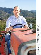 Купить «Confident male owner of vineyard driving tractor outdoors in sunny day», фото № 28073818, снято 22 января 2018 г. (c) Яков Филимонов / Фотобанк Лори