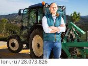 Купить «Confident male owner of vineyard posing near tractor outdoors in sunny day», фото № 28073826, снято 22 января 2018 г. (c) Яков Филимонов / Фотобанк Лори