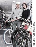 Купить «Cheerful couple in helmet standing near bicycle», фото № 28073862, снято 8 января 2018 г. (c) Яков Филимонов / Фотобанк Лори