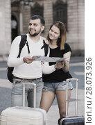 Купить «Happy tourists with map and baggage outdoor», фото № 28073926, снято 25 мая 2017 г. (c) Яков Филимонов / Фотобанк Лори