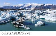 Купить «Amazing view of floating icebergs in the glacial lake Jokulsarlon on the background of blue sky, Iceland», видеоролик № 28075778, снято 15 октября 2017 г. (c) Алексей Кузнецов / Фотобанк Лори
