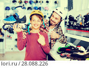 Купить «Father and son showing roller-skates they bought in sports store», фото № 28088226, снято 21 декабря 2016 г. (c) Яков Филимонов / Фотобанк Лори