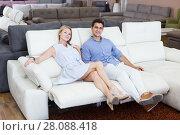 Купить «Smiling spouses testing new sofa-transformer», фото № 28088418, снято 19 июня 2017 г. (c) Яков Филимонов / Фотобанк Лори