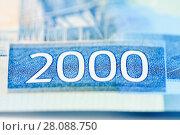 Новая купюра 2 тысячи рублей крупным планом на белом фоне. Фрагмент с цифрой 2000 на деньгах. Стоковое фото, фотограф Игорь Низов / Фотобанк Лори