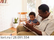 Купить «Grandfather And Grandson Reading Book At Home Together», фото № 28091554, снято 1 сентября 2016 г. (c) easy Fotostock / Фотобанк Лори