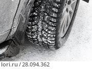 Купить «Car wheel on snow tire with metal studs», фото № 28094362, снято 27 февраля 2018 г. (c) EugeneSergeev / Фотобанк Лори