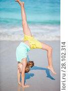 Купить «Active little girl at beach having a lot of fun. Cute kid making sporty exercises on the seashore», фото № 28102314, снято 3 января 2018 г. (c) Дмитрий Травников / Фотобанк Лори