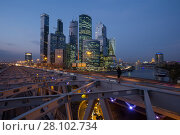 Купить «MOSCOW - SEP 18, 2015: Man stands on railway bridge and shoots Moscow International Business Center and quay at evening. Investments in Moscow International Business Center was approximately 12 billion dollars», фото № 28102734, снято 18 сентября 2015 г. (c) Losevsky Pavel / Фотобанк Лори