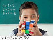 Купить «Close-up of girl solving Rubik cube in a classroom», фото № 28107990, снято 6 июня 2014 г. (c) easy Fotostock / Фотобанк Лори