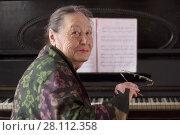Купить «Old smiling lady pianist seating at the piano», фото № 28112358, снято 20 февраля 2018 г. (c) Константин Шишкин / Фотобанк Лори