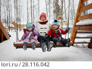 Mother and two children sit on swing on winter day. Стоковое фото, фотограф Losevsky Pavel / Фотобанк Лори