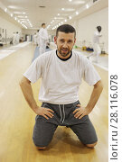 Купить «Man sits in floor in gym for fencing training, other people out of focus», фото № 28116078, снято 9 февраля 2017 г. (c) Losevsky Pavel / Фотобанк Лори