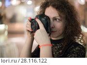 Купить «Curly woman shoots by camera indoor during event, shallow dof», фото № 28116122, снято 18 февраля 2017 г. (c) Losevsky Pavel / Фотобанк Лори