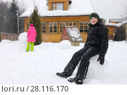 Купить «Boy sits in big snowball, girl makes snowman near wooden country house during snowfall at winter day, girl out of focus», фото № 28116170, снято 24 февраля 2017 г. (c) Losevsky Pavel / Фотобанк Лори