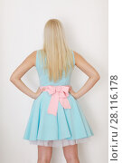 Купить «Young blonde in dress with bow poses near white wall in studio, back view», фото № 28116178, снято 31 октября 2016 г. (c) Losevsky Pavel / Фотобанк Лори