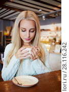 Купить «Young blonde woman sits in cafeteria at table, holding cup of coffee in hands», фото № 28116242, снято 1 ноября 2016 г. (c) Losevsky Pavel / Фотобанк Лори
