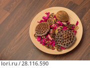 Купить «Dried fruits, citrus, petals of flowers are on plate on wooden floor», фото № 28116590, снято 12 декабря 2016 г. (c) Losevsky Pavel / Фотобанк Лори