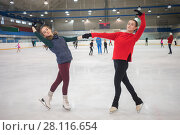 Купить «Two graceful girls pose on skate in indoor ice rink, other people out focus», фото № 28116654, снято 26 января 2017 г. (c) Losevsky Pavel / Фотобанк Лори