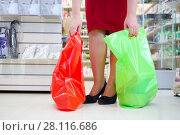 Купить «Lags of woman in red with two bags in modern supermarket with many goods», фото № 28116686, снято 14 октября 2016 г. (c) Losevsky Pavel / Фотобанк Лори
