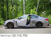MOSCOW - JUN 19, 2016: Silver sportscar with an open door on road in front of green foliage. Редакционное фото, фотограф Losevsky Pavel / Фотобанк Лори