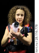 MOSCOW - DEC 13, 2014: Woman with curly hair (with model release) in a special vest with a laser gun in laser tag at the shopping center Capitol Vernadsky. Редакционное фото, фотограф Losevsky Pavel / Фотобанк Лори