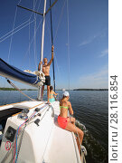 Купить «Happy father, mother and daughter sail on yacht on river at summer day», фото № 28116854, снято 19 августа 2016 г. (c) Losevsky Pavel / Фотобанк Лори