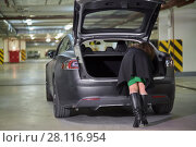 Купить «Young woman rummages in trunk of car standing at underground parking, rear view», фото № 28116954, снято 11 ноября 2015 г. (c) Losevsky Pavel / Фотобанк Лори