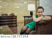 Купить «Woman in green dress sits in armchair in hall», фото № 28117014, снято 13 ноября 2015 г. (c) Losevsky Pavel / Фотобанк Лори