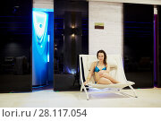 Купить «MOSCOW, RUSSIA - NOV 14, 2015: Young woman in  swimsuit sits on lounge under plate with Solarium inscription at recreational area in Radisson Royal Ukraine hotel, one of seven Stalin skyscrapers», фото № 28117054, снято 14 ноября 2015 г. (c) Losevsky Pavel / Фотобанк Лори