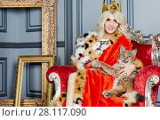 Купить «Young blonde woman in red cloak and crown sits in armchair with lynx cub», фото № 28117090, снято 14 ноября 2015 г. (c) Losevsky Pavel / Фотобанк Лори