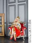 Купить «Young blonde woman in red cloak and crown sits in armchair», фото № 28117094, снято 14 ноября 2015 г. (c) Losevsky Pavel / Фотобанк Лори