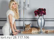 Купить «Young blonde woman stand leaning on table on which lynx cub lies», фото № 28117106, снято 14 ноября 2015 г. (c) Losevsky Pavel / Фотобанк Лори