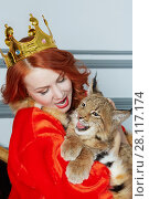 Купить «Red-haired woman in red dress, cloak and with crown on head sits on couch holding lynx cub», фото № 28117174, снято 14 ноября 2015 г. (c) Losevsky Pavel / Фотобанк Лори