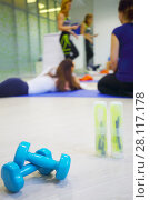 Two skipping ropes, dumbbells are on floor, three women are in hall for fitness out of focus. Стоковое фото, фотограф Losevsky Pavel / Фотобанк Лори
