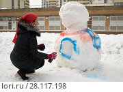 Купить «Young woman paints body of snowman with aerosol spray in courtyard of residential buildings», фото № 28117198, снято 23 февраля 2016 г. (c) Losevsky Pavel / Фотобанк Лори