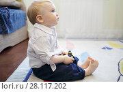 Купить «Handsome little funny blonde boy sits on soft carpet in room and looks up», фото № 28117202, снято 7 мая 2016 г. (c) Losevsky Pavel / Фотобанк Лори