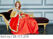 Купить «Red-haired woman in red dress, cloak and with crown on head sits on couch», фото № 28117210, снято 14 ноября 2015 г. (c) Losevsky Pavel / Фотобанк Лори