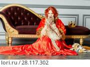 Купить «Red-haired woman in red dress, cloak sits on floor near couch holding lynx cub», фото № 28117302, снято 14 ноября 2015 г. (c) Losevsky Pavel / Фотобанк Лори