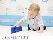 Купить «Happy cute boy toddler plays with toy train on bed in cozy room», фото № 28117318, снято 7 мая 2016 г. (c) Losevsky Pavel / Фотобанк Лори