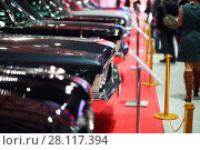 MOSCOW - MAR 07, 2016: Hoods of black shiny cars at exhibition Oldtimer-Gallery in Sokolniki Exhibition Center. It is only one in Russia exhibition of vintage cars and technical antiques. Редакционное фото, фотограф Losevsky Pavel / Фотобанк Лори