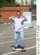 Купить «Happy man points to GyroScooter on street at sunny summer day», фото № 28117430, снято 25 июня 2016 г. (c) Losevsky Pavel / Фотобанк Лори