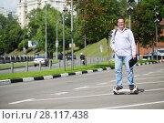 Купить «Happy man with folder rides GyroScooter on street at summer day», фото № 28117438, снято 25 июня 2016 г. (c) Losevsky Pavel / Фотобанк Лори