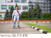 Купить «Man with phone and documents rides on GyroScooter near building at summer», фото № 28117478, снято 25 июня 2016 г. (c) Losevsky Pavel / Фотобанк Лори