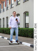 Купить «Happy man with phone rides gyroscooter near building at summer day», фото № 28117494, снято 25 июня 2016 г. (c) Losevsky Pavel / Фотобанк Лори