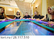 Купить «Five hazardous young people play poker in luxury casino with electronic table, part of this photo in frame», фото № 28117510, снято 24 октября 2016 г. (c) Losevsky Pavel / Фотобанк Лори