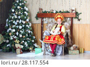 Купить «Girl in Russian traditional costume sits in chair near christmas tree», фото № 28117554, снято 20 ноября 2015 г. (c) Losevsky Pavel / Фотобанк Лори