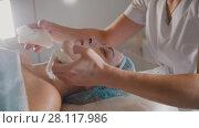 Купить «Woman getting a cosmetic procedure - mask facial massage at spa salon skincare», видеоролик № 28117986, снято 16 августа 2018 г. (c) Константин Шишкин / Фотобанк Лори
