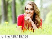 young woman in red dress lying on grass. Стоковое фото, фотограф Иван Михайлов / Фотобанк Лори